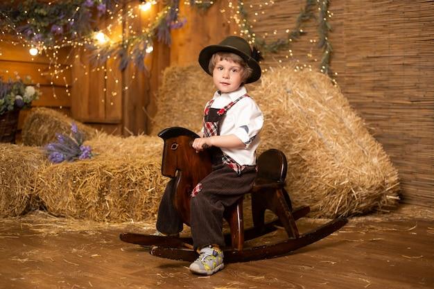 わらの束を持つファームでレトロな衣装を着ておもちゃの馬に座っている笑顔の赤ちゃん
