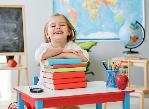 Маленькая улыбающаяся белокурая девушка сидит за белым столом и держит руки на книгах в просторном школьном классе