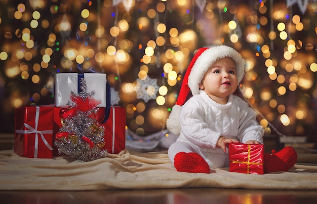 Little smiling boy (baby) in a white knitted sweater and hat of santa claus on a surface of christmas garland and gift boxes with ribbon.