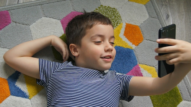 Little smiling  boy hand holding mobile phone or smartphone making selfie portrait photo or video call conference