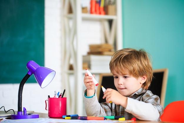 Маленький улыбающийся мальчик учится рисовать в школе.