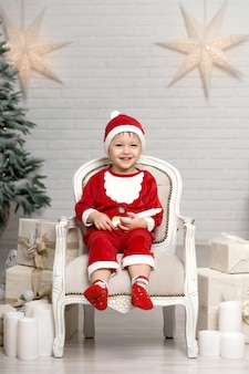 Little smiling boy in santa claus costume sits on armchair near christmas tree and holds white candle in hands