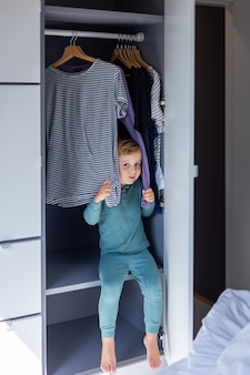 Little smiling boy sitting in the wardrobe and playing in hide and seek. adorable child is playing at home in the wardrobe.