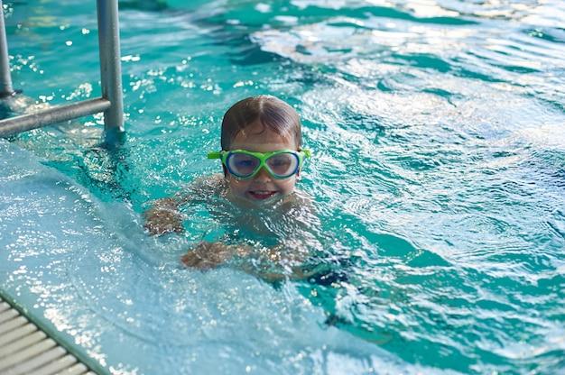 Маленький улыбающийся мальчик плавает в бассейне. крупный план.