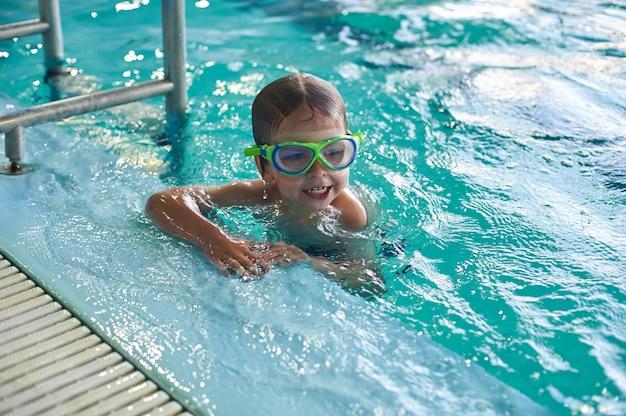 笑みを浮かべて男の子がプールで泳ぎます。閉じる。