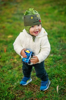 A little smiling boy with two teeth in warm clothes playing with toy car on green grass on the sunset. happy childhood concept.