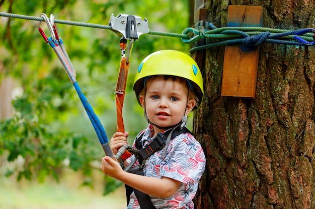 Little smiling child boy in adventure park in safety equipment in summer day