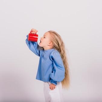 Маленькая улыбающаяся девочка ребенка, держащая чашку, изолированную на белом фоне. студийная съемка