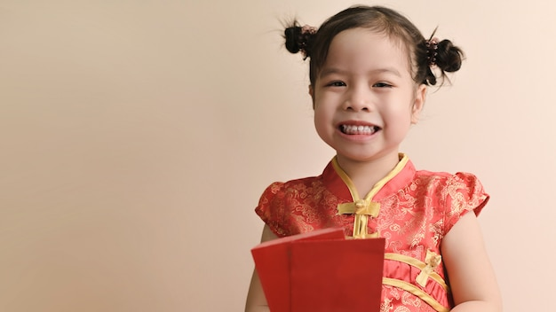 Little smiling curly asian girl hold red envelopes and smile