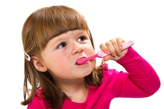 Little smiling curly girl brushing teeth