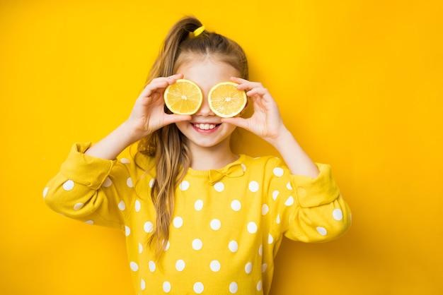 눈 근처에 신선한 신 레몬 과일의 반쪽을 잡고 노란색 배경 위에 혀를 보여주는 노란색 티셔츠에 작은 웃는 귀여운 금발 소녀