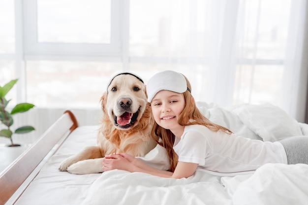 웃는 소녀와 골든 리트리버 개는 눈 수면 마스크를 쓰고 함께 침대에 머물면서 카메라를 바라보고 있습니다. 아침 시간에 애완 동물을 가진 아이의 초상화. 집에서 주인과 강아지