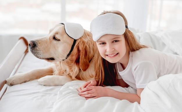 작은 웃는 소녀와 함께 침대에 머물고 눈 수면 마스크를 착용하는 골든 리트리버 강아지. 아침 시간에 애완 동물과 함께 아이. 집에서 소유자와 강아지