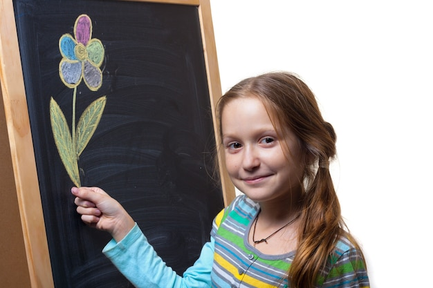 Little smiling girl holding a flower that drawn with chalk on a blackboard