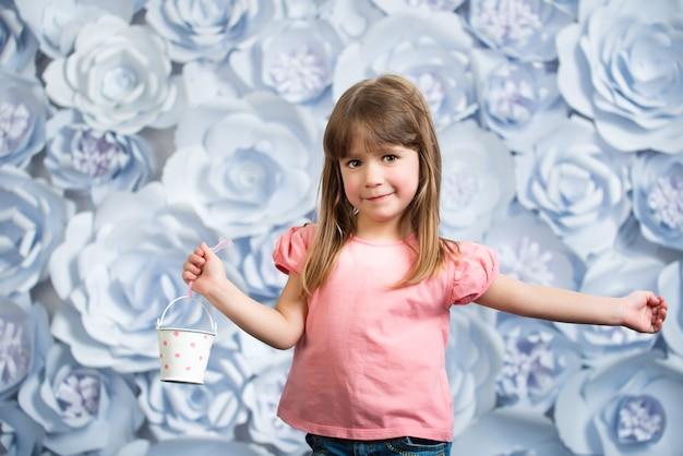 ピンクのブラウスとジーンズの小さな笑顔の女の子は彼の手に小さな装飾的なバケツを持っています