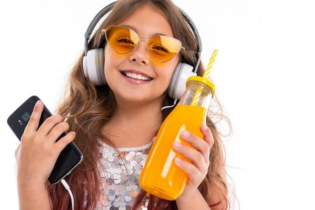 Маленькая улыбающаяся девушка в наушниках слушает музыку в оранжевых очках