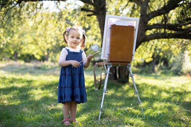 Маленькая улыбающаяся девочка в джинсовом платье, картина в зеленом летнем парке на открытом воздухе. талантливая маленькая девочка-художник, держа в руках кисть, позирует возле мольберта в солнечном весеннем саду.