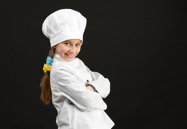 白いシェフの衣装で少し微笑んでいる女の子
