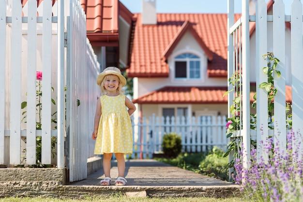 黄色の夏のドレスと白の家の裏庭で麦わら帽子で少し微笑んでいる女の子