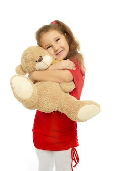Little smiling girl is hugging  with bear in red dress isolated on white