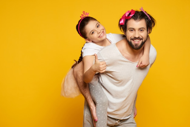 Little smiling girl is riding on fathers back.