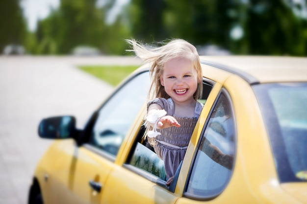 Little smiling girl is sticking her head out the car window and looking at camera