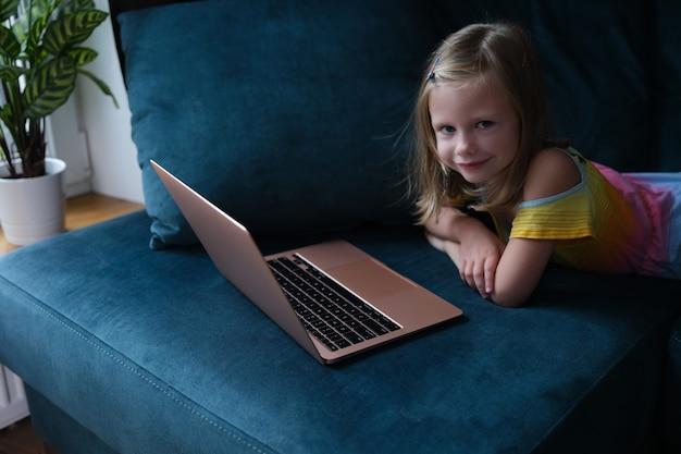 Маленькая улыбающаяся девочка лежит на диване с крупным планом ноутбука