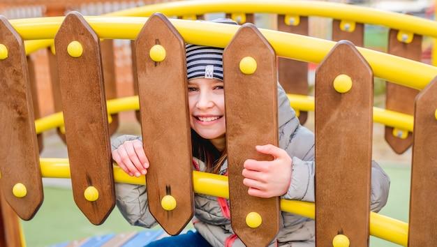 Маленькая улыбающаяся девочка, выглядывающая через деревянный забор на детской площадке