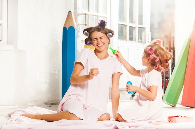 Маленькая улыбающаяся девочка играет с пузырем и ее мать на белом
