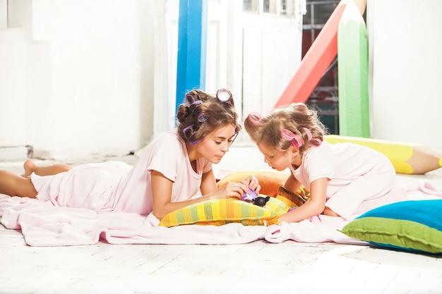 Маленькая улыбающаяся девочка играет со своей матерью на белом