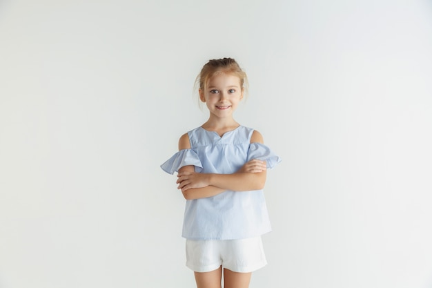 Little smiling girl posing in casual clothes on white studio
