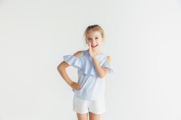 Piccola ragazza sorridente che posa in abbigliamento casual su studio bianco