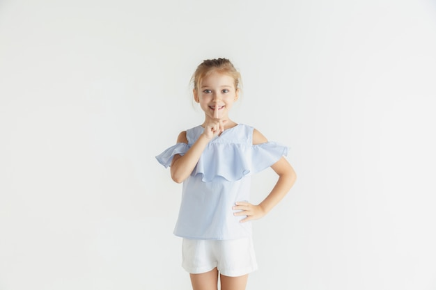 흰색 스튜디오 배경에 캐주얼 옷을 입고 포즈 웃는 소녀