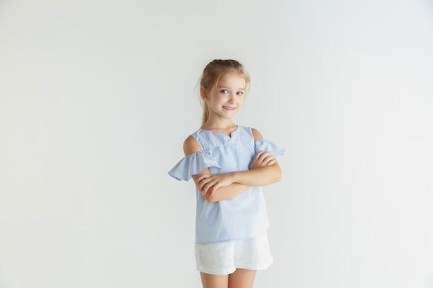 白いスタジオの背景にカジュアルな服でポーズをとって小さな笑顔の女の子