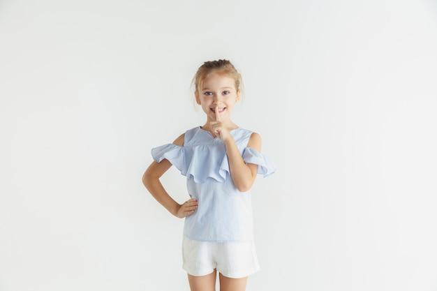 Маленькая улыбающаяся девочка позирует в повседневной одежде на белой студии