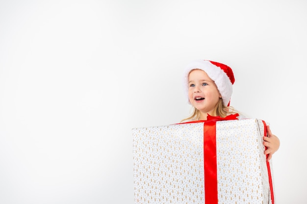 Little smiling girl in santa helper hat holding white gift with red ribbon on white