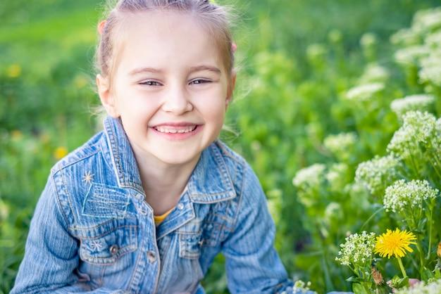 Маленькая улыбающаяся девочка, сидящая в поле травы