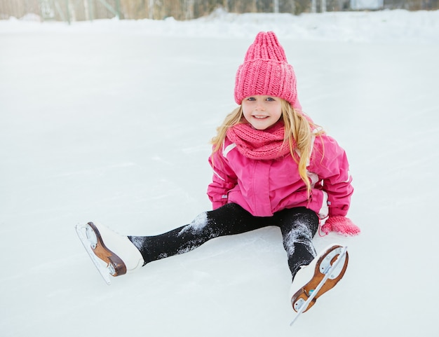 Little smiling girl skate and fell on ice in pink wear. outdoor.