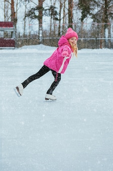 Little smiling girl skating on ice in pink wear. winter
