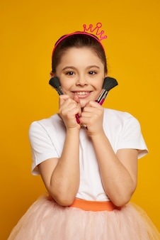 Little smiling girl stands with makeup brushes