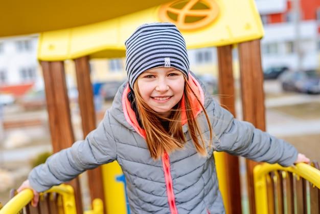 Маленькая улыбающаяся девочка в пальто и шляпе стоит на детской площадке и смотрит в камеру