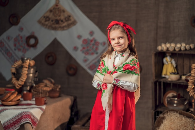赤いヘッドバンドとカーニバルの饗宴を持つテーブルの近くに立ってカメラに微笑んで装飾的なショールを着て少し微笑んでいる女の子
