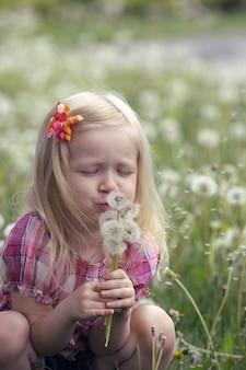 Маленькая улыбающаяся девочка с одуванчиком на траве в парке
