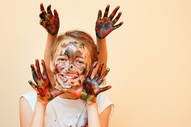 Little smiling girl with sister behind making bunny ears with hands in colorful paints smiling at camera