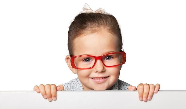 白い空白の小さな笑顔の女の子が背景にクローズアップ
