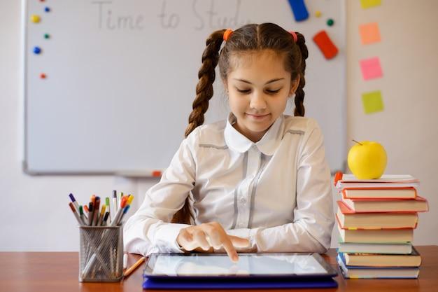 교실에서 태블릿 컴퓨터에서 작업하는 웃는 소녀