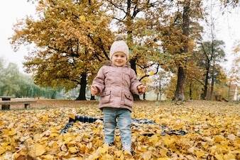 Little smiling kid standing on autumn foliage in park