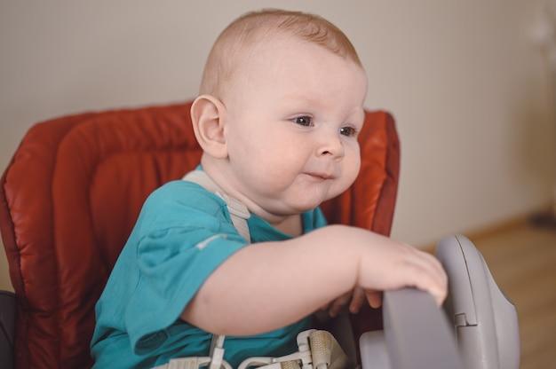 Маленький улыбающийся новорожденный ребенок сидит на стульчике для кормления