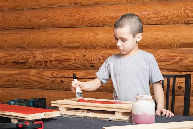 小さな笑顔の幼児の男の子は、赤で手にブラシで木を描く