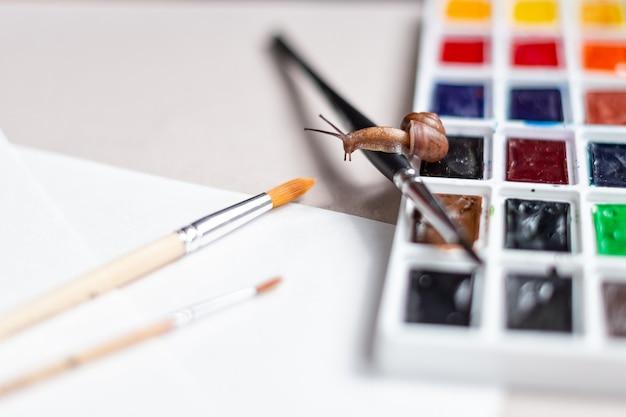 小さなカタツムリが水彩絵の具パレットの上に置く絵筆の上を這います。アートと創造性の概念。テキストのためのスペース